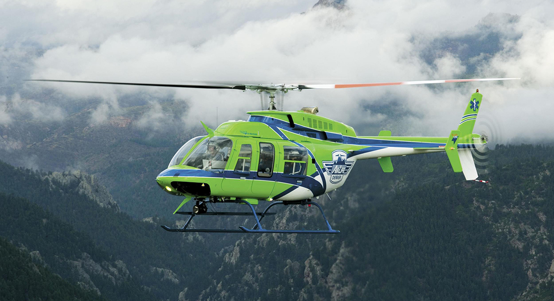 Green Bell 407 helicopter flies in misty mountains