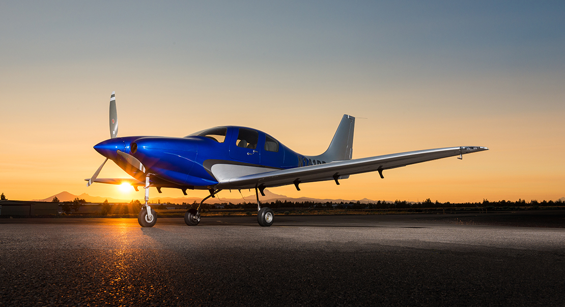 Blue airplane with sunset in the background.