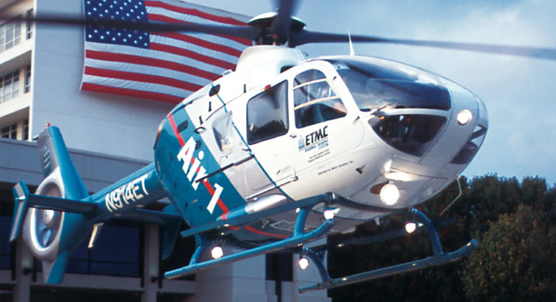 Blue and white helicopter hovers in front of building with American flag in the background.