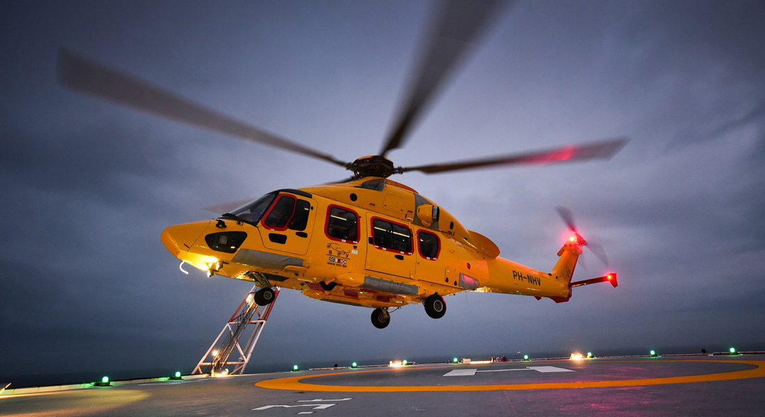Yellow helicopter flies at dusk with lights on.